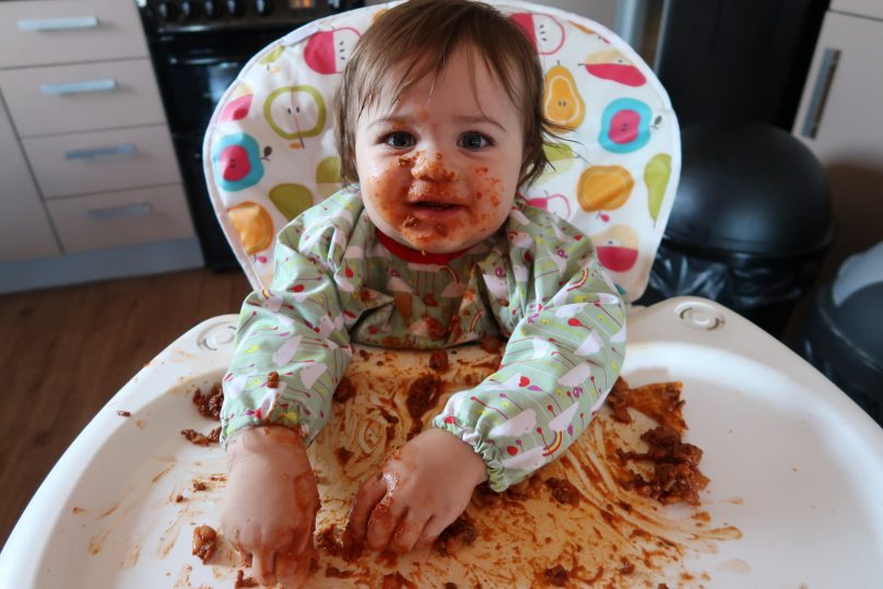 Daisy eating spaghetti bolognese in her high chair